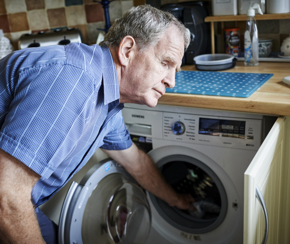 A visually impaired man loading his washing machine