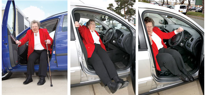 A woman getting into a car by swinging her legs around after she has sat down