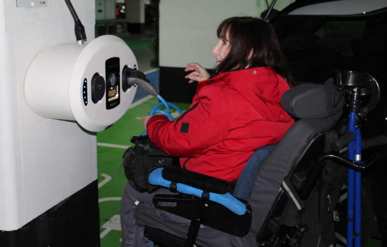 Picture of a RiDC panel member in a wheelchair using an electric car charging point