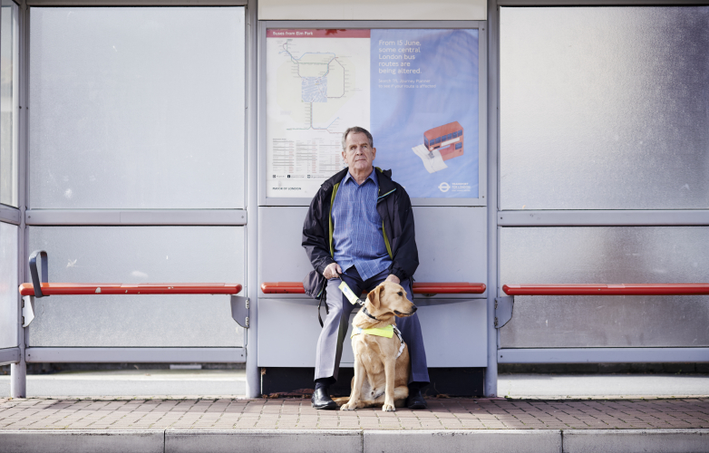 A visually person waiting at a bus stop with his guide dog