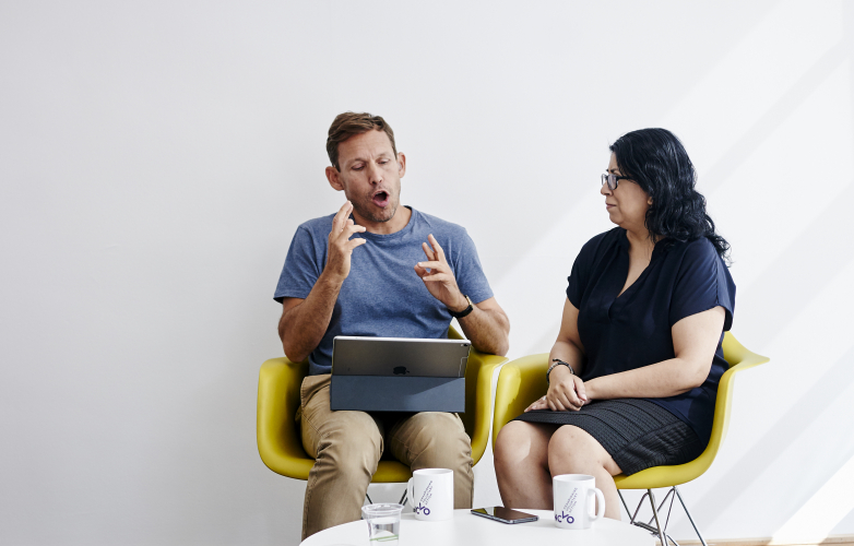 Picture of a man and woman sitting in yellow chairs conversing in British Sign Language