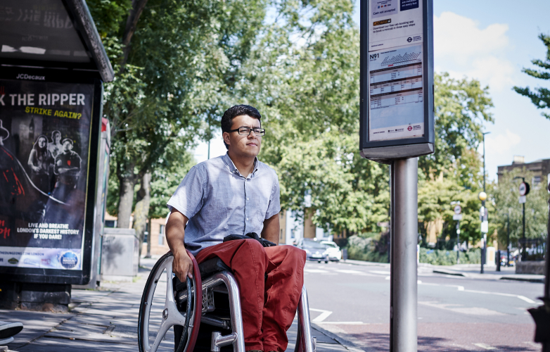 A picture of Pete, a RiDC panel member, waiting at a bus stop in his wheelchair