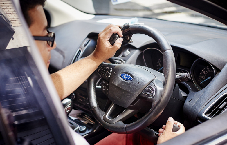 Man in a Ford car with hand controls on the steering wheel