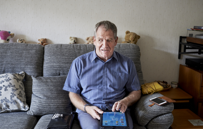 Image of visually impaired man using apps on tablet device at home