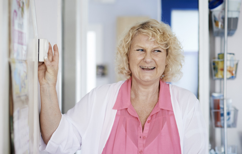 Smiling woman adjusts wall-mounted heating controls