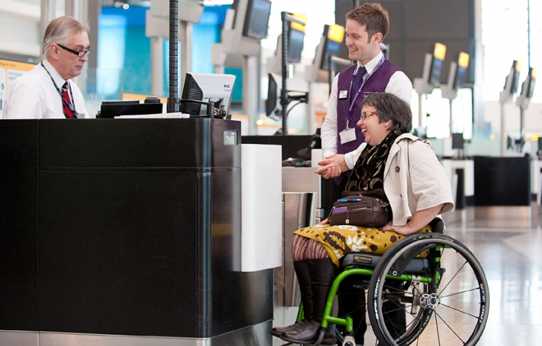 Woman in wheelchair with airport assistant at the information desk