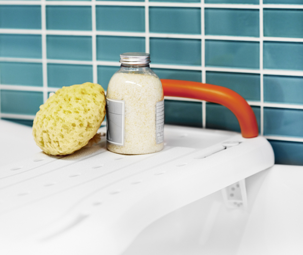 Picture of a bath board, a sponge and a bottle of bubble bath